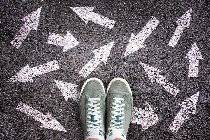 sapatas-e-setas-da-sapatilha-que-apontam-em-sentidos-diferentes-no-asfalto-conceito-bem-escolhido-na-terra-do-142142985-696x465